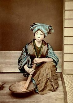 "This is quite a beautiful image of a Geisha (or older Maiko) posing for a ""domestic scene"".    It hand-tinted albumen print was taken in the 1880s by a relatively obscure but active photographer named YAMAMOTO."