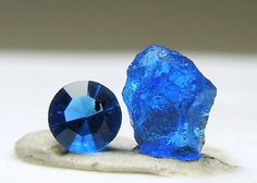 A set of rough and cut with a round gem and a transparent piece of rough.   Both piece is an electric blue color. The gem is 0.04 ct.   Haüyne is an uncommon silicate. Measures for the rough. From Germany.