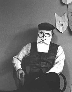 Saul Steinberg wearing one of his masks, c. 1961. Photo by Inge Morath. © Estate of Inge Morath/Magnum Photos.