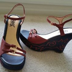 """CARLOS BY CARLOS SANTANA """" STRUT"""" WEDGES CARLOS BY CARLOS SANTANA """" STRUT """" WEDGES IN DENIM BLUE AND RED WITH GOLD HARDWARE WITH A FLAME LIKE DESIGN ON OUTER SIDE OF EACH SHOE. THESE ARE FUN, FUN!! 5 IN HEIGHT. Carlos Santana Shoes Wedges"""