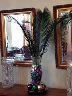 Easy centerpiece idea - this one is for Mardi Gras! peacock feathers instead, also other cheaper feathers + mardi gras colored flowers.