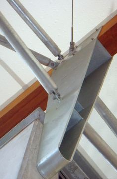 Detail showing a typical connection juncture between fabric canopy, glulam beams, cross bracing pipes and cables and attachment to base structure at the cornice line. Bent plate bracket is bolted through to precast structural column.