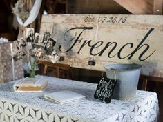 For a very country-chic look, consider decorating your venue with upcycled materials. To make their gifts table pop, this smart couple incorporated their last name and wedding date by painting an old door.