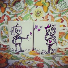 Cute hand painted his and hers coffee mugs.White ceramic mugs with robot love illustration. Handwash only.