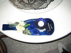 Tuikkualusta tehty lasipullo sulattamalla ja koristelemalla keinokukkasin