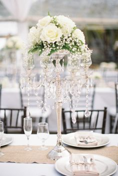 A classic crystal candelabra with white roses: http://www.stylemepretty.com/florida-weddings/florida-keys/islamorada/2014/09/08/elegant-florida-keys-wedding-at-the-caribbean-resort/ | Photography: Bob Care - http://careweddings.com/