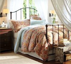 The openwork design of the bed conveys a sense of lightness that's enhanced by the sunlight pouring through the window behind it. The paisley duvet cover and pin-tucked quilt showcase rich, warm color while lending incredible softness to the bed. The deep wooden tones of the bedside table and end-of-bed bench complete the space with a grounding effect.  Benjamin Moore™ Paint Color:  OC-15 Baby Fawn