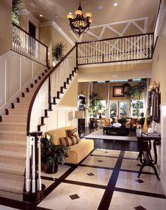 Luxury home with straight staircase landing at the front of a foyer.  Foyer contains armless sofa and leads into the two-story living room.