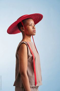 A South African woman wearing a red hat shot against a blue background Stylist: Bielle Bellingham Photographer: Micky Wiswedal Hat: Crystal Birch Red Hats, African Women, Blue Backgrounds, Stylists, Women Wear, The Unit, Stock Photos, Woman, Portrait