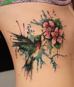 Watercolor hummingbird tattoo. This is similar to what I'm thinking of, I was thinking of the humming bird holding the geranium blossom, but feeding from it is a much better idea. I don't know if I like the background though. But I love the detail on this. Now to find an artist who I able to do a cover-up and do this right. It's a memorial piece, so it has to be done right.