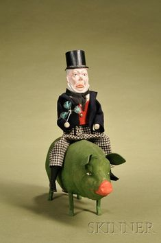 Paddy and the Pig Candy Container, Germany, c. 1915, molded composition bearded Irish gentleman with top hat, carved wood arms and legs wearing wool jacket w/tails, cotton hounds-tooth pants holding a clover, riding atop a flocked composition pig w/ painted eyes and snout, candy container opens underneath belly, lg. 12, ht. 12.5 in.