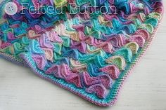 Made with textured motifs that are joined-as-you-go this colorful and unique blanket reminiscent of waves on the sea can be made in any size you wish. The sample blanket detailed in the pattern is perfect for a baby, but can be made to any dimensions you wish.