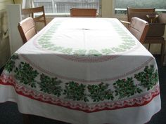 """Oval Christmas Tablecloth Holly with Stylized Poinsettias Green Red White 56"""" X 84"""". $26.95, via Etsy."""