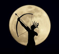 A full moon rises behind a statue of a Kansas Indian on top of the Kansas Statehouse.