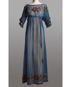 Afternoon dress by  Paul Poiret,1908. Collection Musée Galliera. Canvas blue silk flowers applications silk satin red and yellow trimmings son metallic gold, metallic silver tassels son. © Copyright Photography / Paris City Hall.