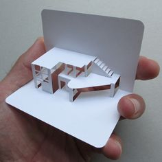modern house shown - in contrast to the stariotypical a frame building. modern design is effectivly portrayed via paper cut out
