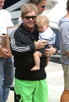 Elton John holds his son Zachary Jackson Levon Furnish-John (b. December 25, 2010) before boarding a yacht in the Sydney Harbour for a party. Once on board John friends who fawn over Zachary. Before disembarking the boat, baby Zachary is handed overboard to a waiting assistant.