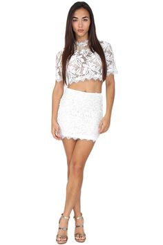 White lace crop top featuring high neckline. If you are in the mood for a fun clubbing night, this sexy top will be your new go-to! Pair with a high-waisted lace skirt and heels for an extra touch of elegance.