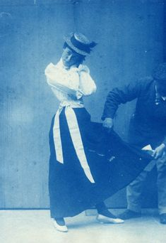 These blue-tinged photographs are cyanotypes, a  kind of print suitable for the cost-conscious amateur. The  image is of Sambourne's daughter Maud striking a pose he subsequently used in a cartoon.  1906