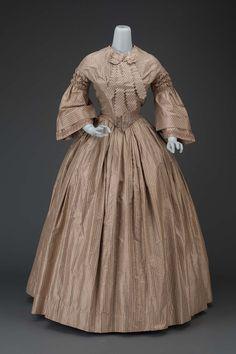 Mid-19th century, America - Dress - Silk taffeta with silk galloon, cotton-serge lining, whalebone, metal hook and eye closure, and self-fabric bow and ribbon ornament