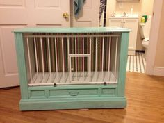 dog house made from old TV console. The gate is removable. The outside is painted robin's egg blue. One coat to create the distressed look. The inside is white and the back particle board is wrapped in striped fabric.