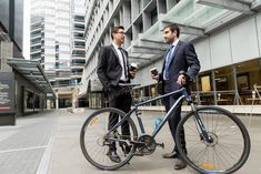 Two young businessmen with a bike in city centre photo by nexusplexus on Envato Elements