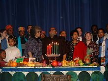 """On December 26, 1966 Kwanzaa was first celebrated by Ron Karenga.  His goal was to """"give Blacks an alternative to the existing holiday and give Blacks an opportunity to celebrate themselves and their history, rather than simply imitate the practice of the dominant society."""" It is inspired by African """"first fruit"""" traditions, and the name is derived from the name for the Swahili first fruit celebration, """"matunda ya kwanza."""""""