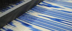 Blue ikat in the loom. // Our collection of Mallorcan fabrics gain their inspiration from the beauty of the forms of the Serra de Tramuntana, the exceptional range of mountains which surround us. A paradise of nature, full of colour and subtlety in which the rising peaks describe the island's visual profile.