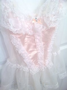 This pink teddy is absolutely adorable, featuring a pretty, pink, lace bodice with frills of lace running up the middle and sides and a frilly lace collar topped with a bow. The sides and flared skirt are a sheer off white. Peeking out from beneath the skirt are four garters.   This piece is ab...