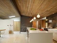 Warm modern kitchen.  White quartz countertops with a Waterfall edge.  Love the wood ceiling.