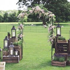 An outdoor aisle of dreams. Made with rustic wooden crates, lanterns and the sweetest floral arch. Plus you NEED to see the centrepieces....