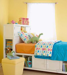 Surround a kid's bed with smart storage solutions. A mix of open cubbies and cabinets with doors provides plenty of options to store belongings and keep the room looking tidy./
