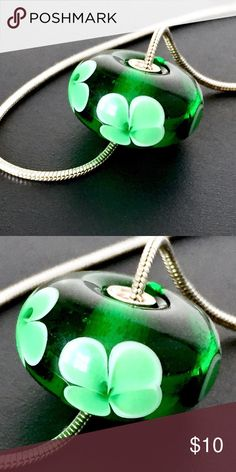 """Blown Glass Bead Lucky Clover Green w/ Silver Core [More photos to come, chain not included, sorry] Lampwork glass bead featuring a deep emerald green with 4 petal floral design smooth on the surface. 18mm (just under 3/4"""") in diameter with 2.5mm hole (fits 2mm snake/omega chain but not Pandora). I use glass from Murano, Italy and work it in a torch flame in my FL studio to form these beads. My glass goes immediately from torch to kiln for an overnight anneal for stability and strength. Core…"""