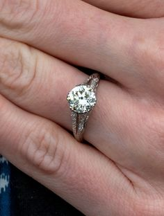 This beautiful vintage 1.6 carat diamond engagement ring dates from the 1940s and features a split band with filigree and diamonds in platinum. . Sku EJ17900