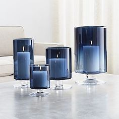 We've added the allure of deep blue to our popular London glass hurricane, a Crate and Barrel classic. Handcrafted large glass hurricane is a modern classic look with a straight-sided silhouette on a short pedestal base. Blue Candle Holders, Hurricane Candle Holders, Hurricane Glass, Modern Candle Holders, Candle Holder Decor, Blue Living Room Decor, Bedroom Decor, Blue Kitchen Decor, Living Room Candles