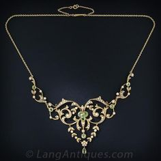This lacy and feminine, turn-of-the-century, peridot and natural pearl necklace displays both Edwardian and Art Nouveau design characteristics. This ravishing and romantic gift comes nestled in its original heart shaped box - circa 1900.