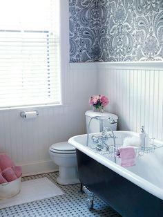 Gorgeous pink & black bathroom with claw foot tub, marble basketweave tiles floor, beadboard backsplash, white & black damask wallpaper and pink accents.