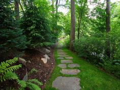 15 Design Ideas for Beautiful Garden Paths: Large, field-collected Pennsylvania stepping stones are sunken in a grassy corridor to create a mosaic effect. The path has a slightly Old World feel that suits the dreamy, enchanted-forest setting.  From DIYnetwork.com