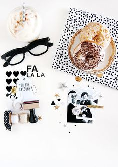 Black and white flat lay with doughnuts, glasses and stationery.