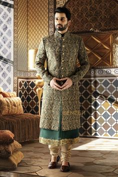 BOTTLE GREEN RAW SILK SHERWANI The unique concept of sherwani over kurta is a mark of exquisite style.Made in raw silk this bottle green sherwani with heavy embroidery detailing is bound to make you the man of the evening! Indian Wedding Suits Men, Sherwani For Men Wedding, Sherwani Groom, Mens Sherwani, Indian Wedding Outfits, Couple Wedding Dress, Groom Wedding Dress, Wedding Attire, Indian Groom Dress