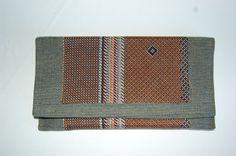 Cartera de mano vaquera con doble tela estampada en tonos marrones y cierre de imán. P.V.P: 25€