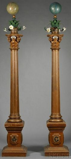 Pair of 19th century carved and polychrome painted Masonic columns [lodge artifact], found in Indiana, the columns surmounted by celestial and terrestrial globes over baskets issuing floral and foliate devices, fluted columns, and square monument bases. Each column is in five pieces.
