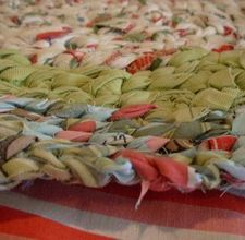Braided rug. These instructions are kind of unclear, but the colors are pretty.  You could make this using recycled thrift store clothing - they always have a bunch of those broomstick skirts in beautiful fabrics.
