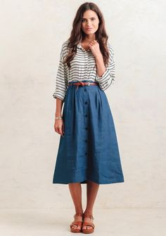 Classic and feminine, this blue cotton skirt features a flared midi silhouette with blue button closures down the front. Finished with side pockets, this lightweight skirt is perfect for creati...