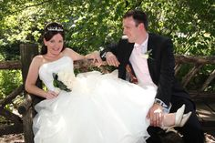 bride and groom relaxing on a rustic bench in Shakespeare Garden in Central Park