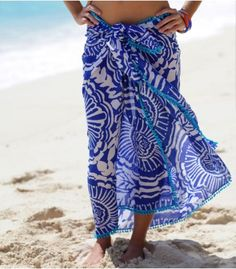 """The floral and ethnic inspirations of the Maria Pareo provide the perfect sarong to cover-up in style. Wear short or long depending on your mood.  By Echo Beach.  Pareo with bobble tassels.  Made of Poly Spun.  Size 44"""" x 64"""".  Model is 5'4/163cm and a standard UK 8/US 4."""