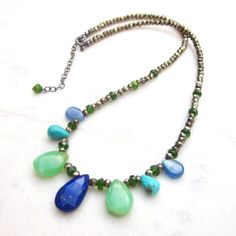 This multi briolette choker necklace features a variety of gemstones in a wonderful combo of green and blue shades, accentuated by the unique metal sparkle of pyrite. The middle gemstone is a faceted intense blue lapis lazuli briolette, embraced by smooth natural Australian chrysoprase pear stones, genuine turquoise and kyanite drops, along with faceted pyrite and electric green chrome diopside rondelles. Chic, modern and very stylish, it closes with an oxidized sterling silver spring ring…