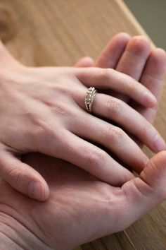 Silver Engagement Ring on the Ring Finger and Two Hands Attached