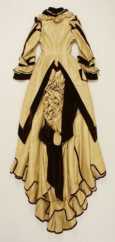 Dress Date: 1872–74 Culture: American Medium: silk, cotton Dimensions: (a) Length at CB: 18 in. (45.7 cm) (b) Length at CB: 60 in. (152.4 cm) Met Museum.
