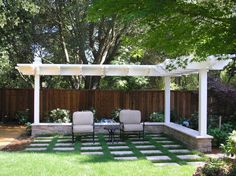 An L-shaped eyebrow arbor w/ posts set in a seat wall frame the lawn area & defines a space for chaises | Menlo Park | Landsystems